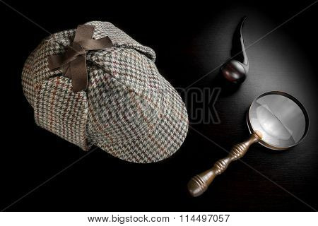 Deerstalker Hat Smoking Pipe Old Key And Vintage Magnifying Glass On The Black Wooden Table Background. Overhead View. Investigation Concept.