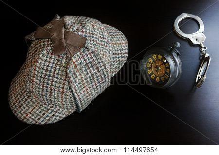 Deerstalker Hat Hand Cuffs Vintage Retro Clock On The Black Wooden Table Background In The Back Light