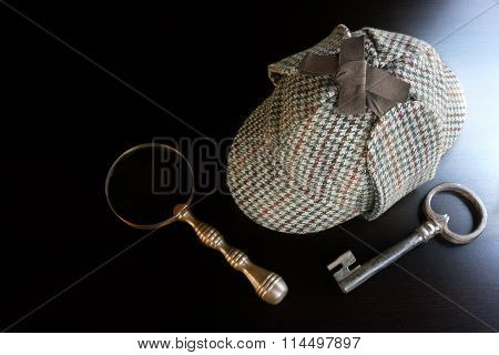 Deerstalker Hat Old Key And Vintage Magnifying Glass On The Black Wooden Table Background. Overhead View. Investigation Concept.