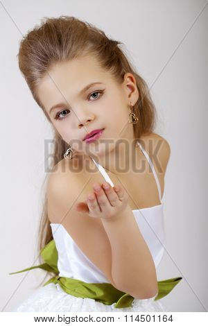 Portrait of a little girl in white classic dress, isolated on gray background