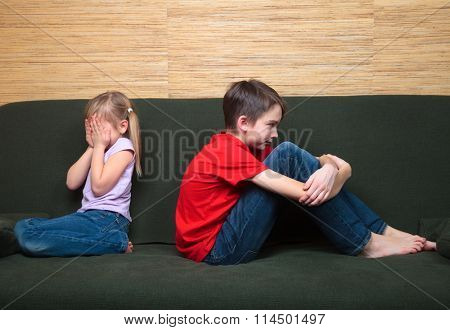 Brother and sister  wearing casual clothes  sitting on a green couch back to back arter fight. Girl covers her face with hands