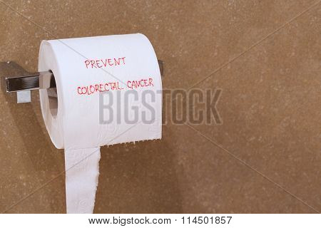 The words prevent colorectal cancer is written on a roll of white patterned toilet paper hanging on a holder in a bathroom.Free space for a text.