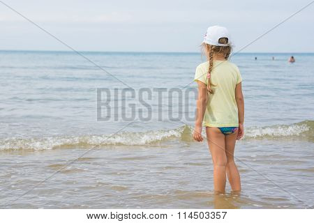 A Girl Stands On The Shore And Looks Into The Distance To The Sea
