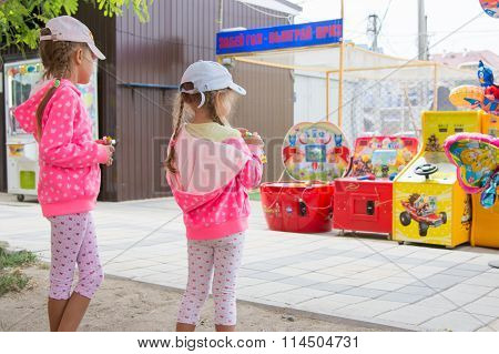 Two Girls Look With Interest At The Children Slot Machines
