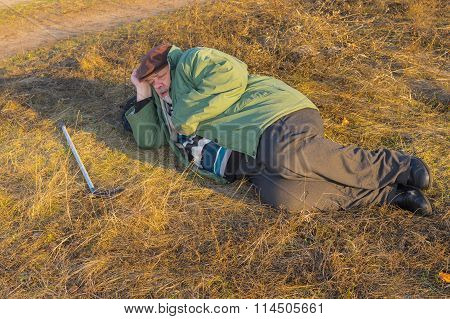 Senior hiker has short rest lying on the roadside