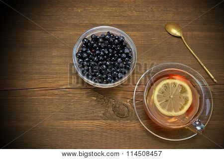 Glass Teacup, Gold Teaspoon, Bowl With Huckleberry On Wood Table