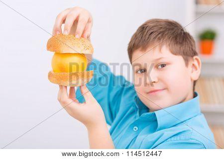 Orange between buns held up by chubby kid.