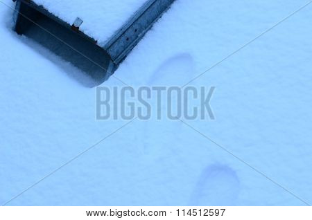 Snow-covered roof and tracks in snow and old dormer.