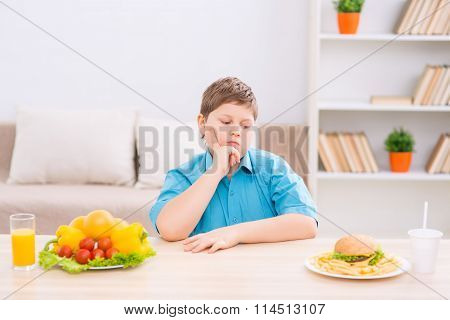 Chubby kid choosing food at the table.