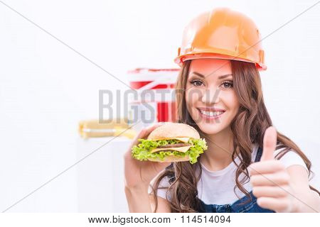 Girl is holding a burger and showing thumbs up.