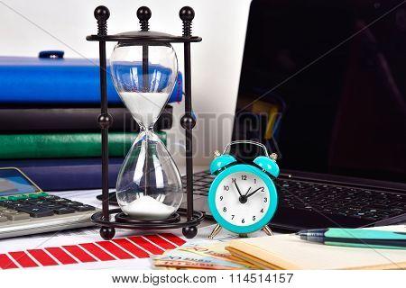 Alarm Clock, Sandglass And Finansical Report