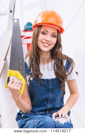 Girl in male role is upholding a saw.