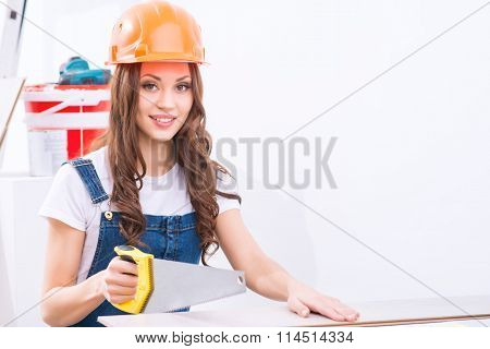 Girl in male role is busy sawing.