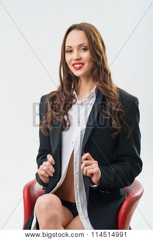 Girl in male role is on the chair.