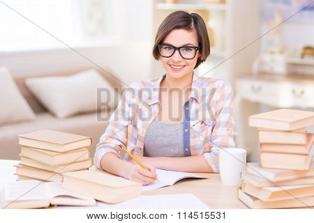 Student is busy studying at the desk.