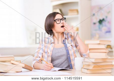 Young student girl is yawning during studying at home.