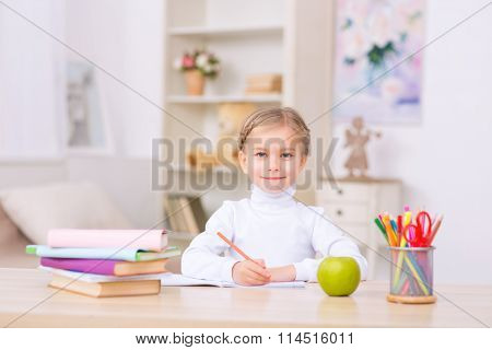 Little girl is sitting at the desk and doing homework.