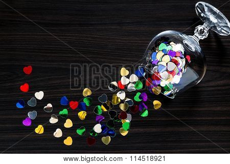 Bright Confetti Heart-shaped Scattered From A Wineglass