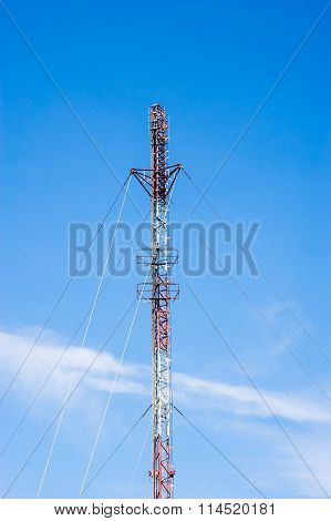 Tall Red And White Antenna On Blue Sky