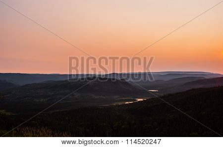 Hills Receding Into Hazy Distance Under Orange Sky