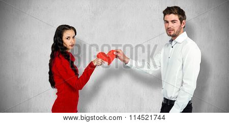 Portrait of couple holding red cracked heart shape against white and grey background
