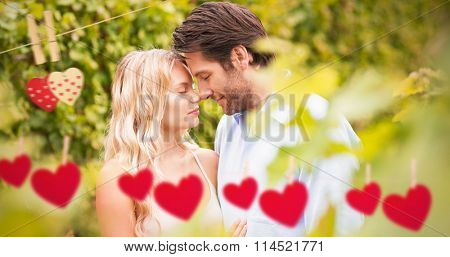 Young romantic couple embracing each other against hearts hanging on a line