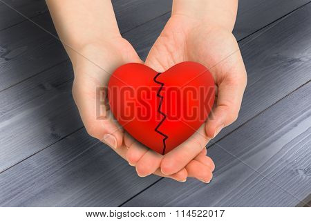 Couple holding broken heart in hands against bleached wooden planks background