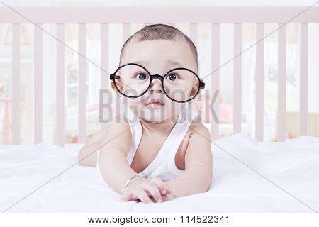 Cute Baby Wearing Glasses In Bedroom