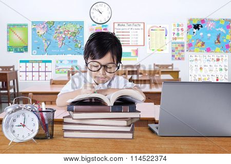 Cute Little Girl Studying In The Classroom