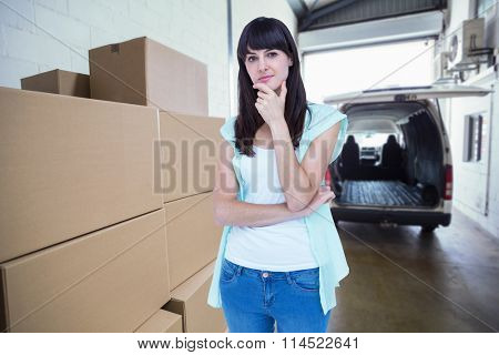 Portrait of beautiful woman with hand on chin against empty van ready to be loaded
