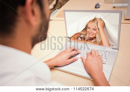 Smiling woman under a duvet against cropped businessman using laptop at desk