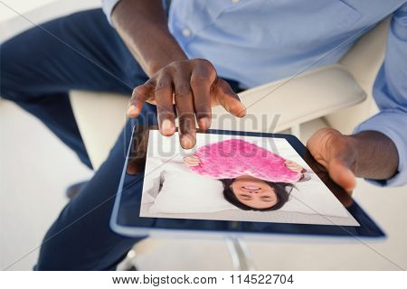 Woman in her bed holding a fluffy heart cushion against businessman using digital tablet while sitting on chair