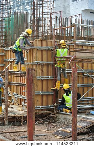 Construction workers fabricating reinforcement concrete wall form work