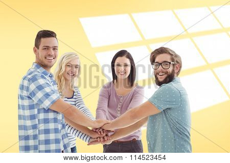 Portrait of smiling business people putting their hands together against yellow vignette