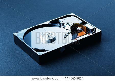 Open Disassembled Hard Disk On Black Plastic Background. Blue Toned Image
