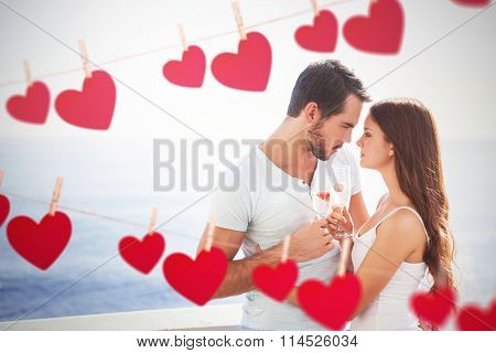 Cute couple toasting with champagne against hearts hanging on a line