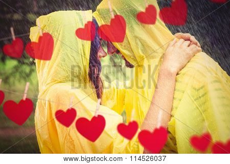 Couple hugging in the rain against hearts hanging on a line