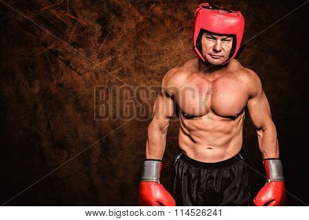 Portrait of shirtless man with boxing headgear and gloves against dark fence
