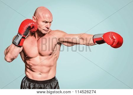 Bald boxer in fighting stance against green background