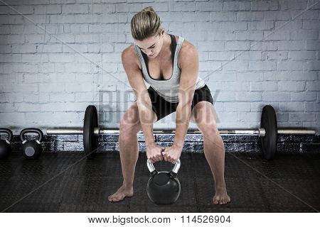 Serious muscular woman lifting kettlebell against gym