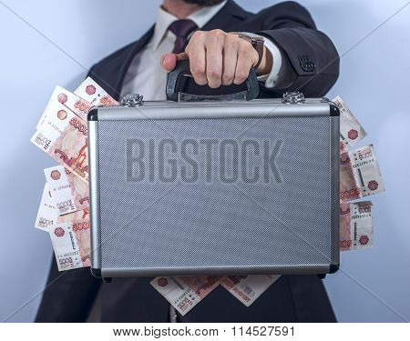 Man in suit holds metal briefcase full of money