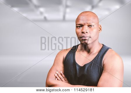 Portrait of bald bodybuilder with arms crossed against white abstract room