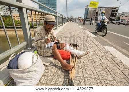 HO CHI MINH, VIETNAM - JAN 14, 2016: Local poor vietnamese man sitting on the street. Located in the South of Vietnam, Ho Chi Minh City is the country's largest city, population 8 million.