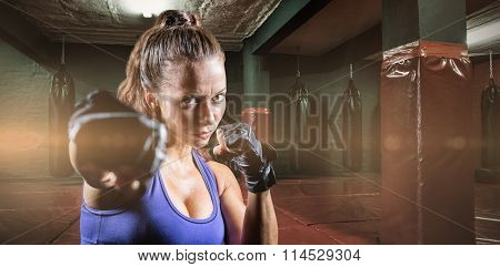 Portrait of female fighter punching against red boxing area with punching bags