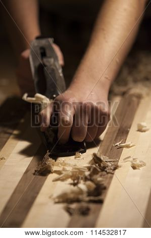 Male hands doing wood work with plane