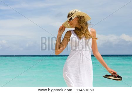 Young woman in a hat on a beach