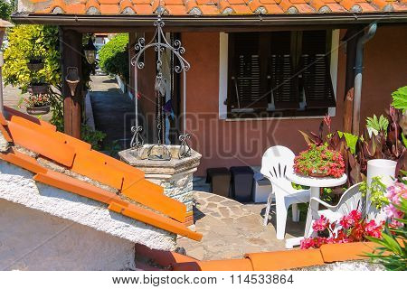 Picturesque Well And Flower Decoration Near Residential House In Small Town Sant Andreas On Elba Isl
