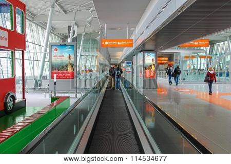Passengers Walking Through Arrival Area Of Warsaw Chopin Airport, Poland