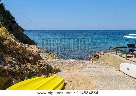 People Taking A Sunbath On The Coast Of The Tyrrhenian Sea, Elba Island, Italy