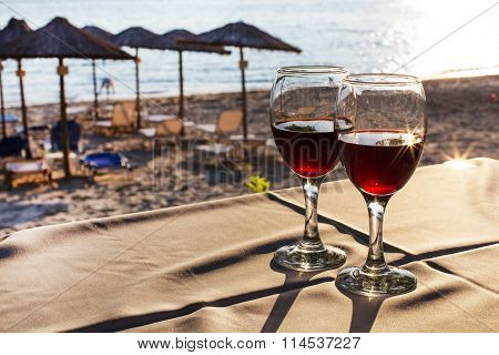 Two glasses of red wine with sun reflection, sea, summer vacation background